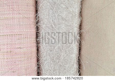 Woolen cotton and twisted cane fabrics of same nude or pink color folded side by side