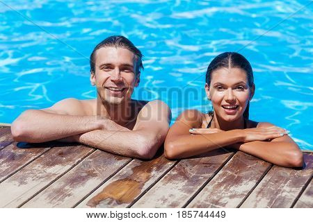 Happy smiling couple looking at camera while relaxing on the edge of a swimmingpool