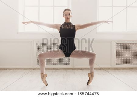 Graceful ballerina practice ballet plie position near large window in light hall. Ballet class training, high-key soft toning, copy space