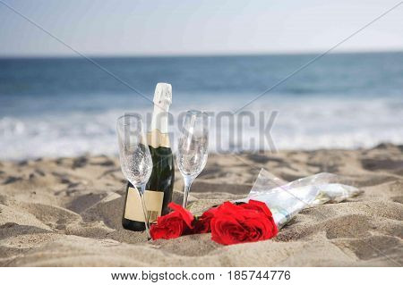 Champagne Bottle, Glasses, Roses at the beach on the sand.