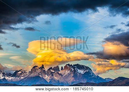 Magnificent cumulus clouds in the rays of the sunset. Torres del Paine National Park. Summer in the south of Chile. The concept of extreme and active tourism
