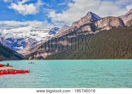 Lake Louise on a beautiful sunny day. The lake is surrounded by mountains, glaciers and pine forests. Banff National Park, Rocky Mountains, Canada