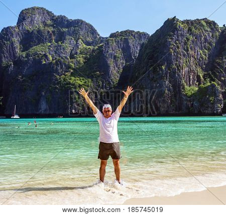 Cheerful elderly man standing in sea water at the beach in Thailand