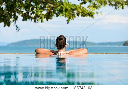 Relax and spa concept. Woman with a flower in hair relaxing in a pool at Krabi Thailand.