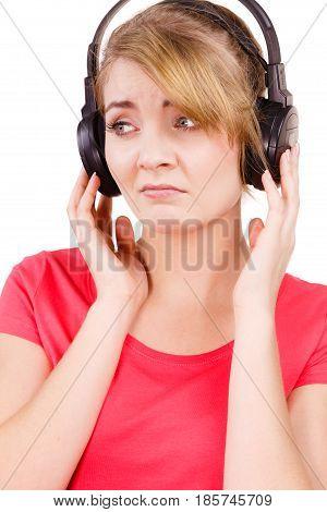 Woman sad unhappy girl in big headphones listening music mp3 closeup on white. Broken heart love concept