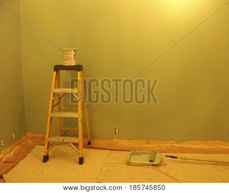 Ladder, paint, brushes & roller in room being painted