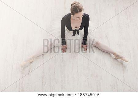 Classical Ballet dancer. Beautiful graceful ballerine in tutu skirt practice split ballet position, top view on white