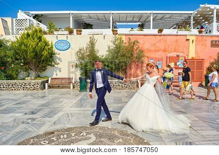 SANTORINI, GREECE - AUGUST 05, 2015: young bride in white dress and bridegroom on Santorini