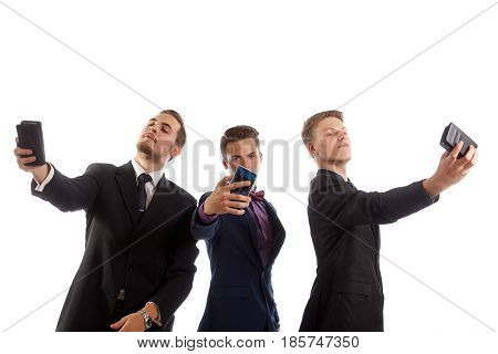Three guys wearing suits making selfies on white background