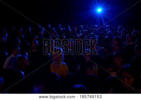 Shot of a dark cinema auditorium full of kids watching a movie together film projector light beam copyspace background layout people children dark interesting entertaining activity lifestyle concept.