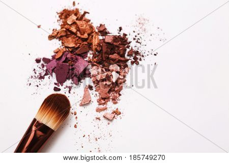 Makeup brush with blush of everyday palette tones sprinkled on white. Make up and female cosmetics background