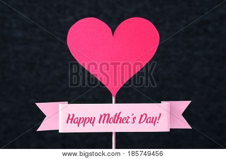 Happy Mother's Day text on a ribbon and red heart shape cut from cardboard on wooden stick. Nice simple greeting design for Mothers Day card or social media campaign for business. Dark background.