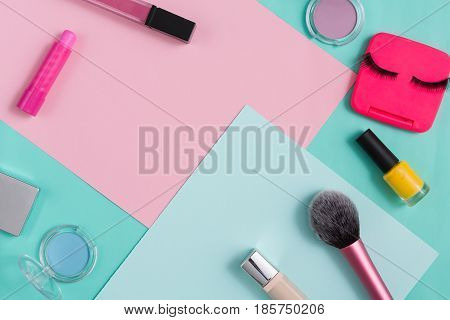Female cosmetics, everyday make-up. Essentials - eyelashes, eyeshadow, lipstick and nail polish on bright background, flat lay, top view