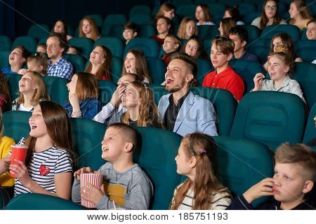 Happy little kids laughing watching a comedy movie at the local cinema people exciting amazing emotional expressive funny positivity leisure hobby lifestyle concept.