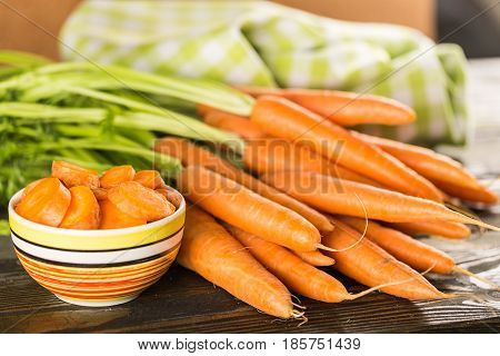 Whole carrots and a bowl of sliced carrots on a table