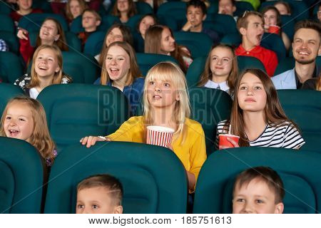 Cinema auditorium full of children during cartoon premiere people lifestyle leisure activity weekend holidays teens preteens fun hobby films relaxing comfortable carefree positivity concept.