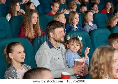 Cute little girl smiling to the camera sitting on the lap of her father at the cinema watching a movie parent fatherhood leisure childhood kids preschool expressive emotions fun popcorn.
