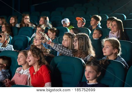 Young girl laughing pointing at the screen while watching a movie at the local cinema children weekend holiday entertainment kids carefree teens fun comedy cartoon concept.
