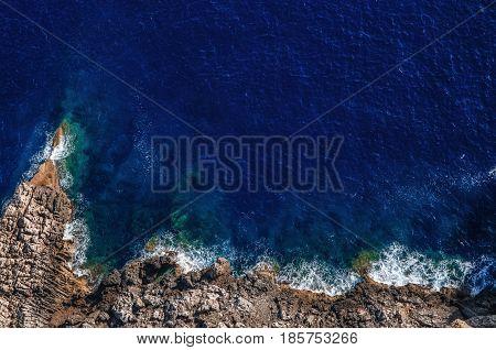 Waves breaking on the shore rocks with sea foam Mallorca