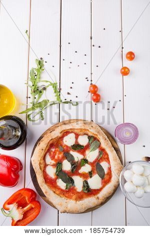 Whole neapolitan pizza served on wooden board