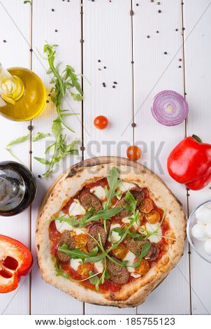 Whole neapolitan pizza with sausages and arugula
