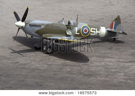 A British Spitfire fighter plane stands ready for action on an oil-stained airfield. poster