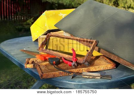 Various hand tools and parts of a bee hive laid on the table outdoor
