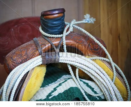 A Green and White Saddle Blanket a Rope Lariat and an Engraved Saddle in Detail