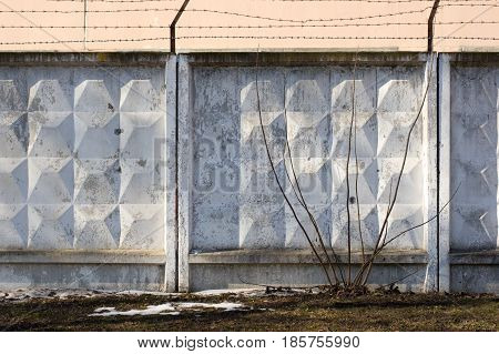 Concrete Fence With Barbed Wire Around The Perimeter. Territory Fencing.