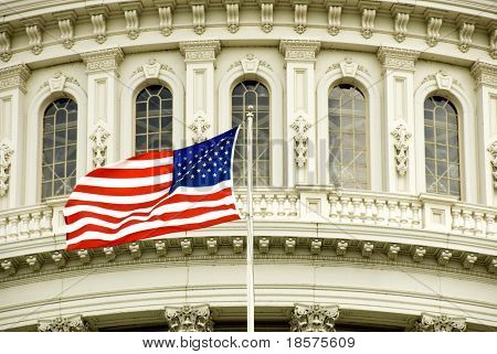 The flag of the USA flying in front of the Capitol building in Washington, DC.