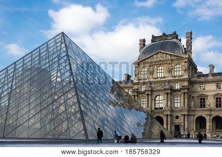PARIS FRANCE - OCTOBER 11 2015: The Louvre Pyramid is a large glass and metal pyramid in the main courtyard of the Louvre Palace in Paris France