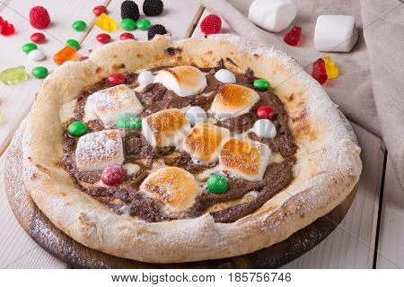 Whole sweet pizza served with marshmallows and candies