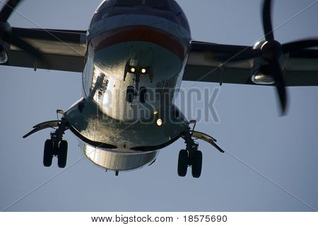 A twin-engined turboprop passenger plane landing at dusk. poster
