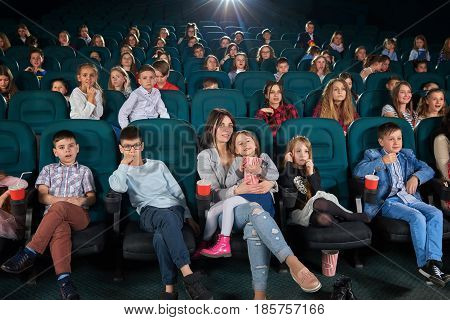 Young woman holding her little daughter on her lap sitting comfortably at the cinema enjoying a movie together people lifestyle entertaining activity leisure hobby happiness positivity concept.