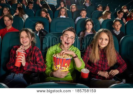 Young boy laughing cheerfully enjoying a funny movie at the cinema with his friends eating popcorn positivity happiness vitality laughter comedy fun people children classmates friendship concept.