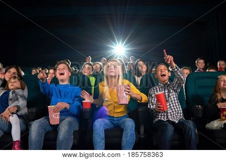 Low angle shot of cinema hall full of children enjoying a movie together copyspace background people kids youth lifestyle positivity expressive emotional entertaining fun activity concept.