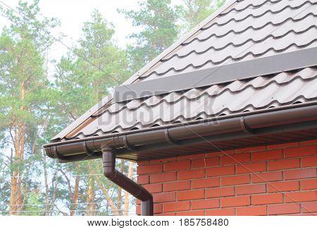 Rain Gutter Pipeline System Installation. Roofing Construction. Rain gutter system and roof protection from snow (Snow guard). Home Guttering Gutters Guttering & Drainage Pipe Exterior.