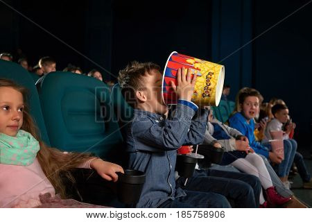 Young boy eating popcorn greedily from a big bucket sitting at the movie theater food snacks hunger corn hungry greedy entertainment delicious tasty childhood junk food concept.