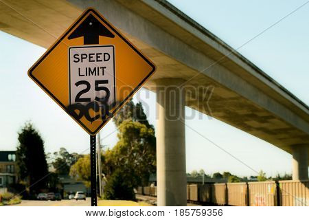 Speed limit sign under freeway with arrow