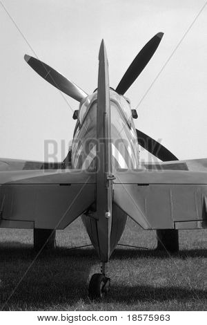 Tail of a mark IX British Spitfire parked beside a grass runway. poster