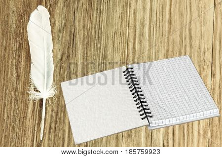Open writing notebook and white feathers on wooden table.Retro style toned image.