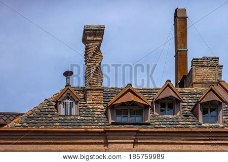Tiled roof of an old house with skylights and pipes in the center of Tbilisi