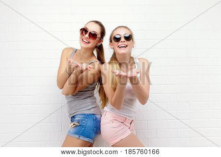 Fashion portrait of two friends posing. modern lifestyle. two stylish sexy hipster girls best friends ready for party. Two young girl friends standing together and having fun.
