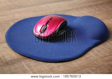 Modern wireless mouse and pad on wooden background