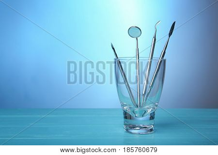 Dental equipment in glass on color background