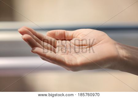 Female hand with needles for acupuncture on blurred background