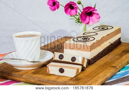 Three-layer chocolate cake, decorated with chocolate patterns. Background - vase with flowers and porcelain cup with tea.  Holiday cake Three-colate. Professional bakery