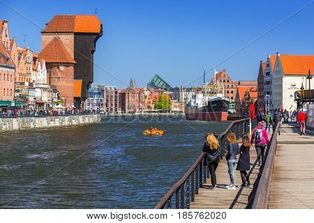 GDANSK, POLAND - MAY 2, 2017: Tourists st the port crane in old town of Gdansk. Port crane in Gdansk built between 1442 and 1444 is the city symbol and the oldest surviving port crane in Europe.