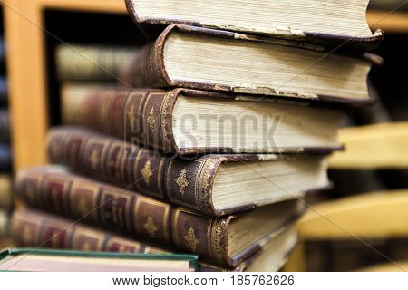 Vintage, antiquarian  books pile on wooden surface in warm directional light. Selective focus