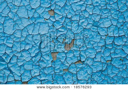 cracked surface of blue paint outdoors